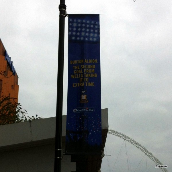 "The banner above was hanging outside Wembley stadium today, and said ""Burton Albion. The second goal from Wells taking it to extra time"". It refers to the game in the fourth round of the Cup, when Wells fired in two goals with only 8 minutes left in the game to force extra-time."