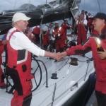 2012 Newport Bermuda Yacht Race - finish. Commodore Jonathan Brewin welcomes George David to Bermuda with a bottle of champagne to celebrate Rambler's record breaking finish.Dateline: 06:09:18 EDT June 17. Bermuda: George David's 90ft maxi Rambler has